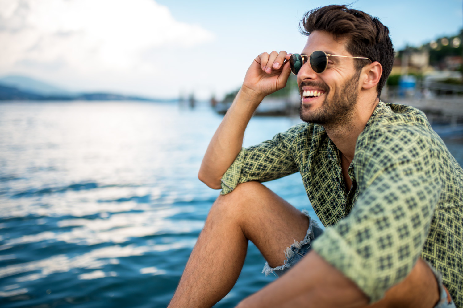 Brunette man wearing a green shirt and sunglasses smiles by a lake with healthier gums in Denver, CO