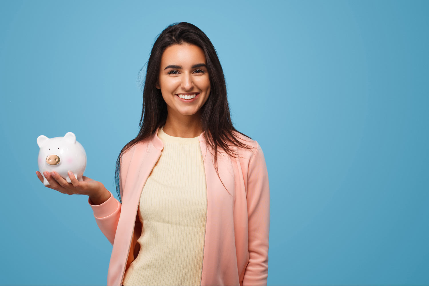 Brunette woman smiles as she holds a white piggy bank because she gets affordable dental care at Vero Dental in Denver, CO