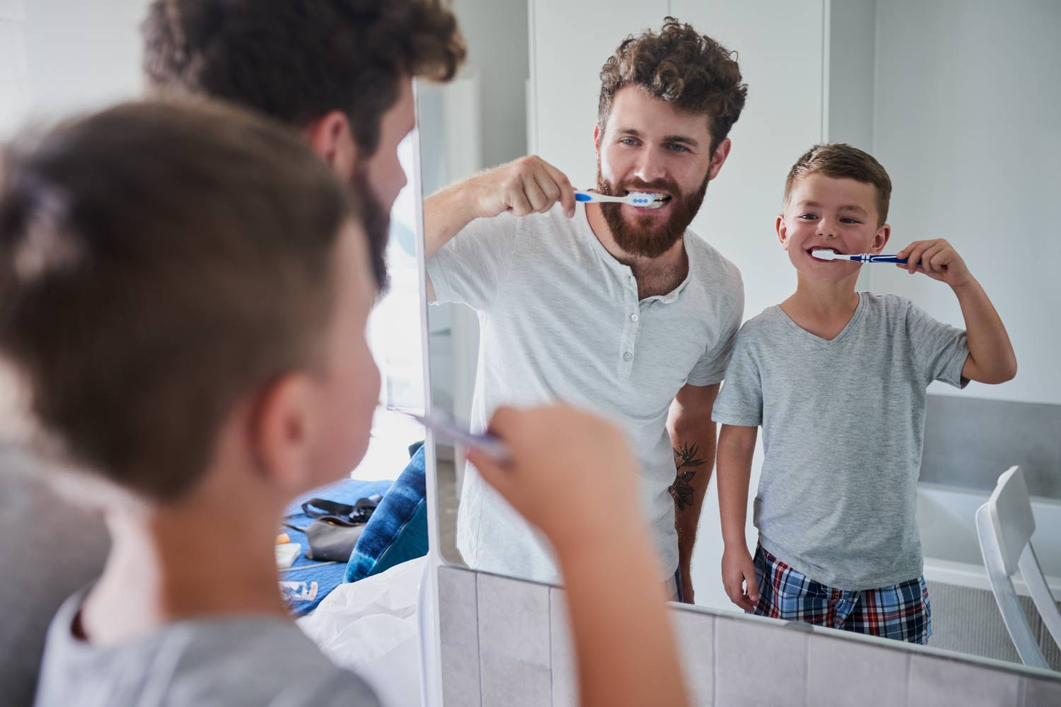 Dad brushes his teeth with his son, making oral hygiene fun for kids
