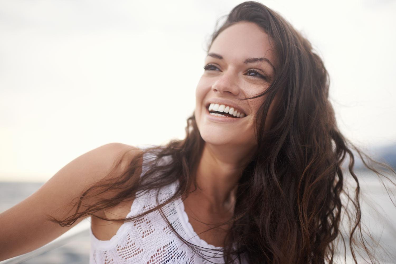 Brunette woman with permanent porcelain veneers smiles in Denver, CO