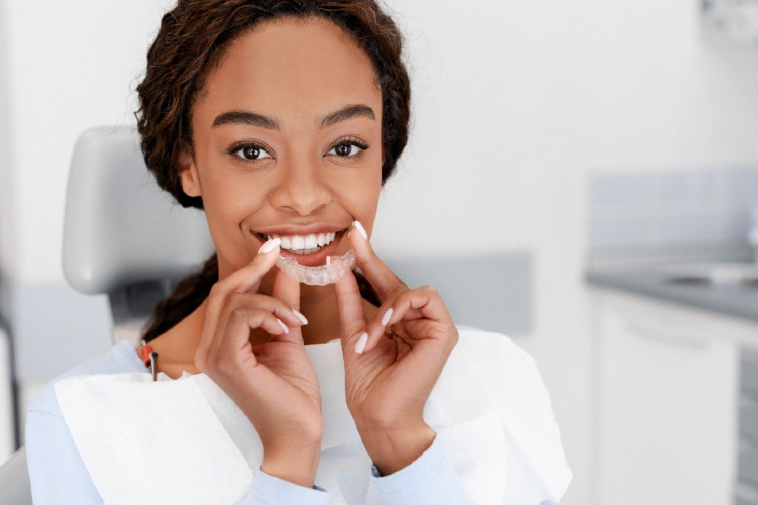 Pretty brown eyed girl holding a clear aligner in front of her smile.