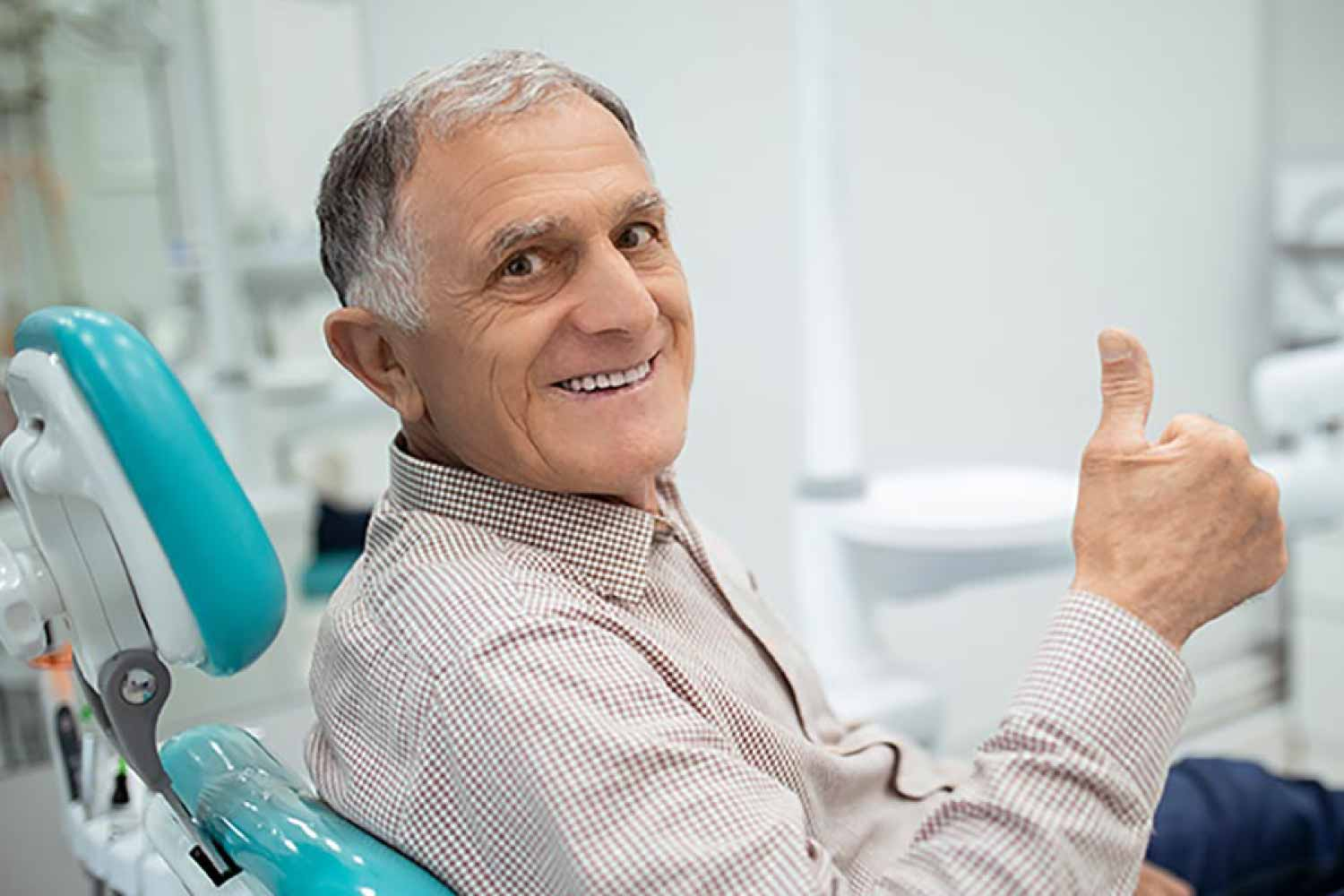 Mature man giving the thumbs up sign from the dental chair.