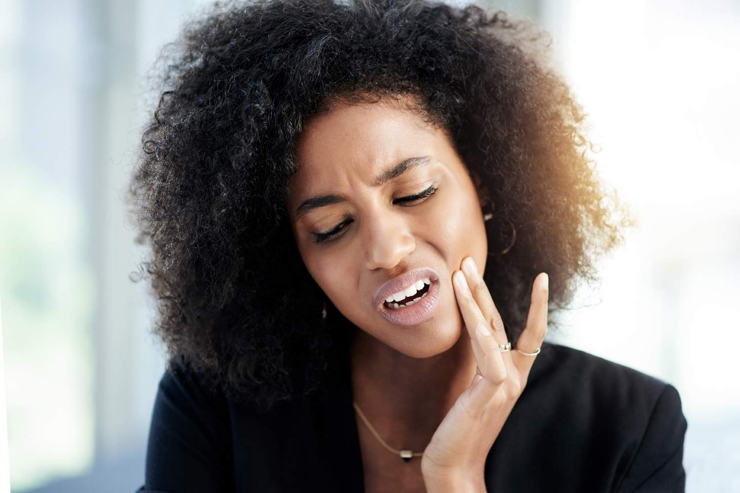 Curly-haired woman in a black shirt cringes in pain and touches her cheek due to a toothache dental emergency